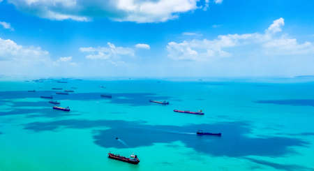 Aerial view of container ships in Singapore Strait. Airplane shot. Cargo ships anchored in the road, waiting to enter the busiest port in region.
