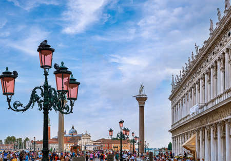 View of Piazzetta of St Marks square, Venice, Italy, full of tourists, evening. Biblioteca Marciana, St Theodores column by waterfront.