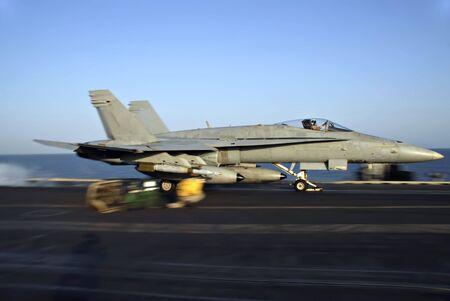 f18: An F-18 Hornet rockets down the deck of an aircraft carrier