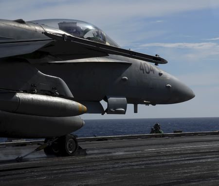 An F-18 Hornet sits moment before being catapulted off the deck of an aircraft carrier