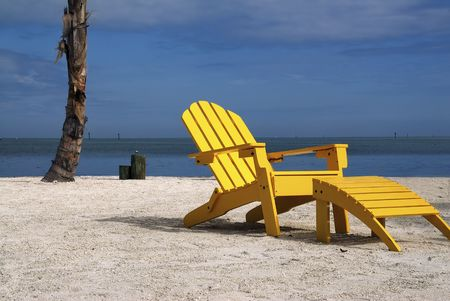 recliner: A wooden yellow recliner sits on a beautiful tropical beach