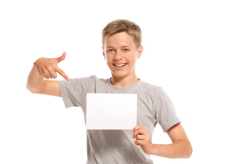 Smiling boy pointing at white blank paper. Isolated on white background
