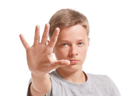 Teenage boy making stop gesture,  isolated on white background