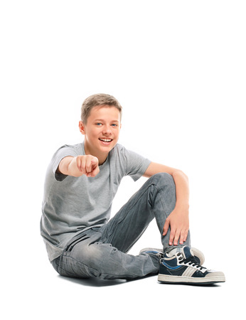 Teenage boy sitting on the floor and points at the camera  Isolated on white background  Stock Photo
