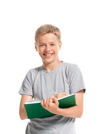 Happy teenage boy writes something in a notebook  Isolated on white background