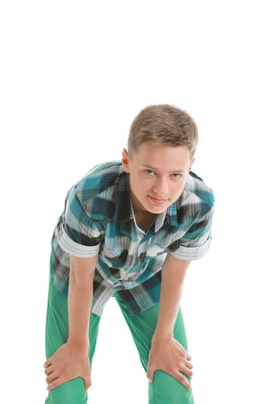 Teenage boy bending forward and looking at camera, isolated on white