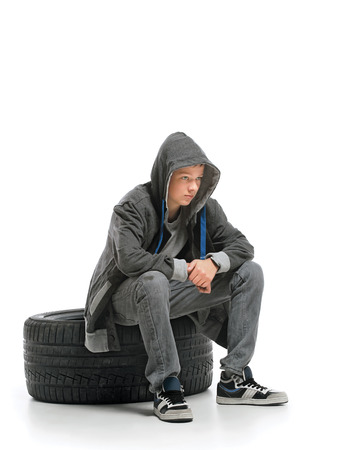 Depressed teenager sits on a tire