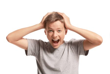 13: Amazed teenage boy holding his head. Isolated on white background Stock Photo