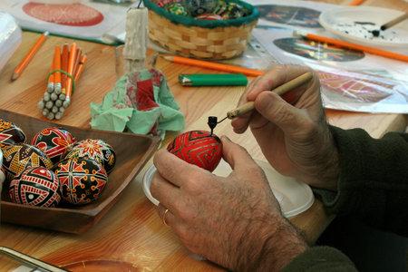 KYIV, UKRAINE - April 23, 2016. VI Ukrainian festival of Easter eggs. A man paints an Easter egg