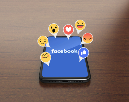 Kiev, Ucrânia - 4 de janeiro de 2018: 3D rendem de um iPhone X preto com aplicação móvel do Facebook na tela com Emoji empático