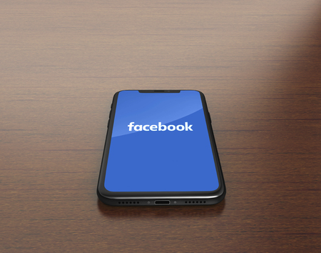Kiev, Ukraine - January 4, 2018: 3D Render of a black iPhone X with mobile application of Facebook Editorial