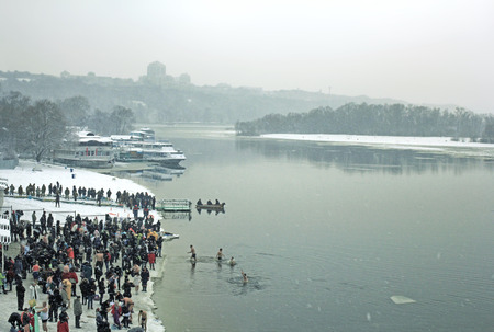 Kiev, Ukraine - January 19, 2018: The feast Epiphany on the icy Dnipro River. Christian holiday created in honor of the event of the history of the Gospel, the baptism of Jesus Christ in the Jordan River by John the Baptist