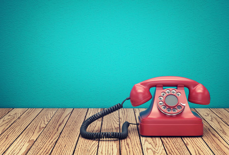 Red rotary telephone on wood table against greenish blue wall background 写真素材