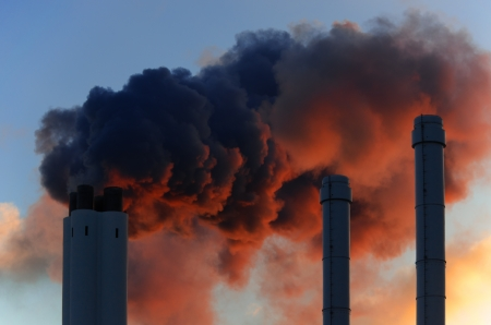 Pollution concept of smoking chimneys The setting sun illuminates the vapor from below, giving it an ominous impression, like that of volcano smoke