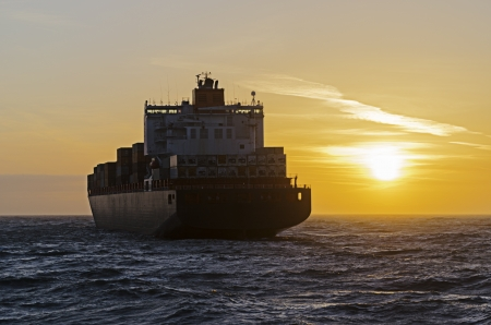 german north sea region: Container ship heading towards sunset on the north sea in Germany