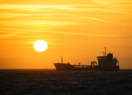 german north sea region: Silhouette of a ship on the north sea in front of a beautiful sunset  Stock Photo