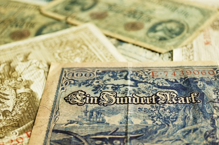 Part of an old German banknote from 1908. Other old banknotes can be seen blurred in the background. Stock Photo