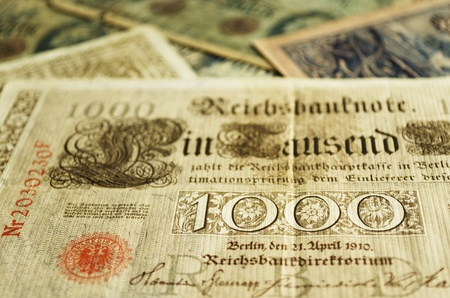 Part of an old German banknote from 1910. Other old banknotes can be seen blurred in the background. Stock Photo