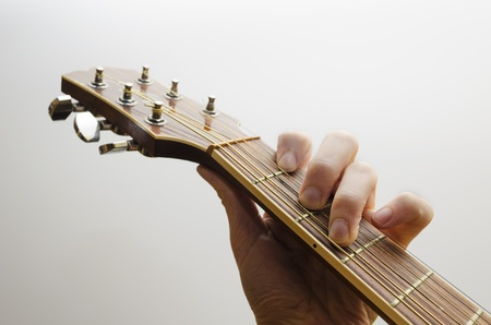 Neck of an acoustic guitar. A hand is holding the C major chord. White backgound.