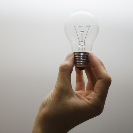 A human hand holding an incandescent light bulb. White backgound.