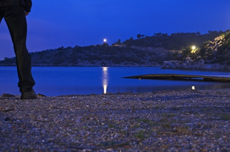poros: A man standing on a lonely beach at night on Poros island in greece