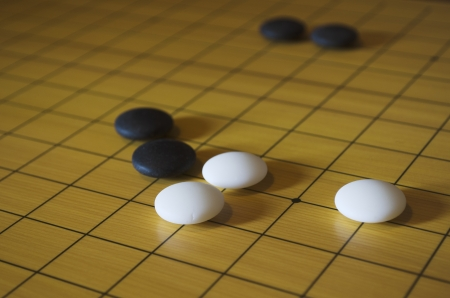 Picture taken during a game of go. Go is an ancient traditional Asian board game. Shallow depth of field. Stock Photo