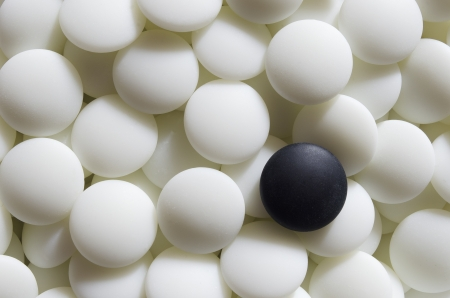 A black go stone lying on a pile of white ones. Go is a traditional Asian strategy game. It is considered to be of the oldest games in the world. Stock Photo