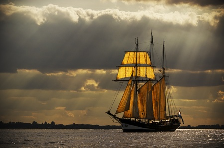 A three-master sailing on the Elbe near Hamburg  The evening light breaks through the gaps in the clouds behind the ship, illuminating the sails from behind  Processed to give it an antique look Stock Photo - 17759942