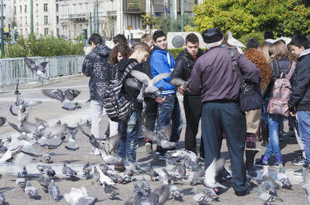 Teenagers buying pigeon fodder from an old man in front of the Hellenic Parliament in Athens.