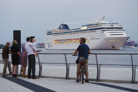 People watching the cruise ship MSC Lirica leave the harbor of Hamburg, Germany.