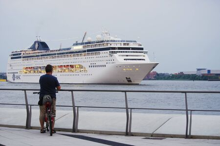 Bicyclist watching the cruise ship MSC Lirica leave the harbor of Hamburg, Germany.