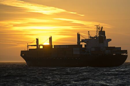 german north sea region: A container ship heading towards sunset on the german North Sea  Stock Photo