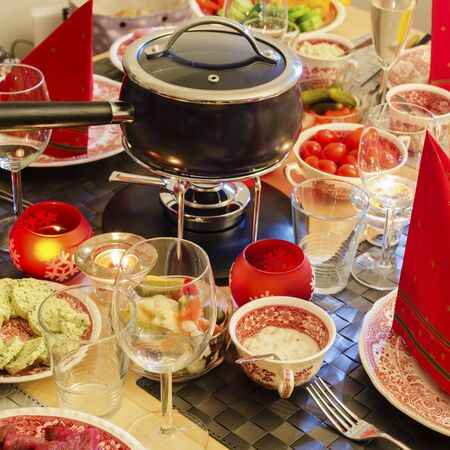 A well-laid table with a fondue caquelon, vegatables and dishes  Square format