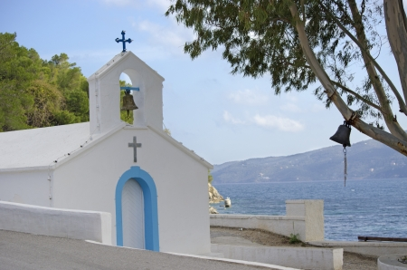 A little white chapel on the island Poros in Greece  The Peleponnese peninsula can be seen in the background