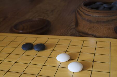 A set of the traditional Asian board game go  A bowl with black stones is in the background  Shallow depth of field