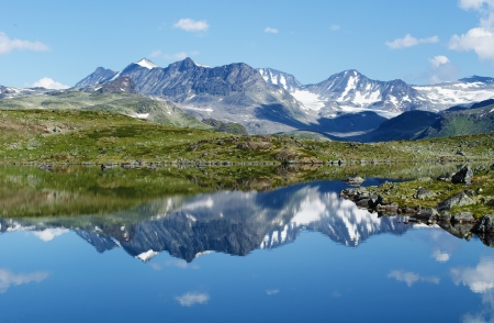 Reflection of mountain chain in a small lake in Jotunheimen national park in Norway  Stock Photo