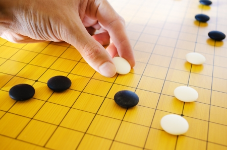 A male hand places a go stone on the board in a game of go  Stock Photo