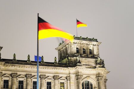 German flag waving above the Reichstag, the german parliament in Berlin  Stock Photo