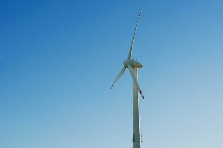 A wind engine in front of a blue summer sky  Horizontal