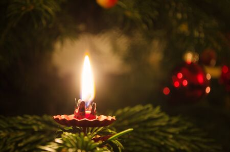 A candle on a christmas tree with decoration in the background  Stock Photo