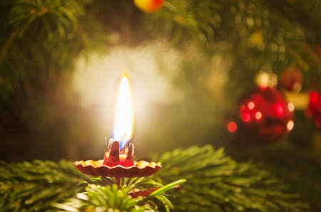 Candle on traditionally decorated christmas tree