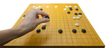 A hand placing a stone on a go board  Go is a traditional asian board game  It is supposed to be one of the oldest games in the world  Stock Photo