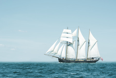 schooner: Three mast schooner under sails on the baltic sea  Cross processed  Stock Photo