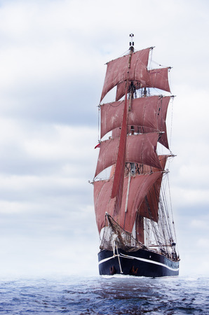 Schooner with beautiful red sails on the baltic sea