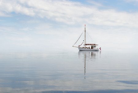 Old cutter anchoring in a misty sea