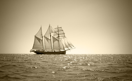 Three mast schooner under sails on the baltic sea. Sepia Toned.
