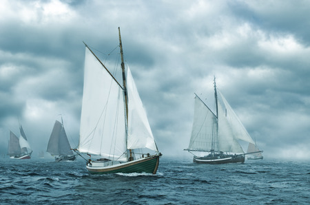 Regatta of old sailing boats coming out of the fog. Stock Photo