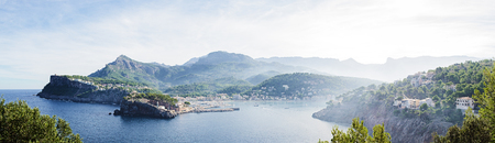 Panoramic image of the bay of Port de Sller on the Iceland Mallorca in Spain. Early morning shot with crap rising from the sea.