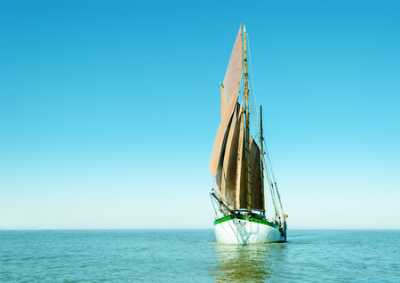 Traditional sailing ship alone on the ocean. Bright image with mainly cyan color. Stock Photo