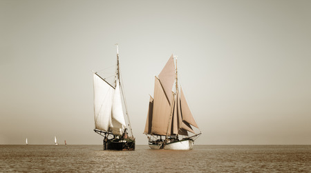 Traditional sailing ships, sailing on the ocean. Sepia toned to give a vintage look. Stock Photo